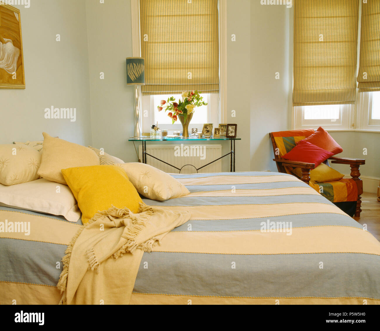 Wide blue+cream striped bedcover on bed in townhouse bedroom with ...