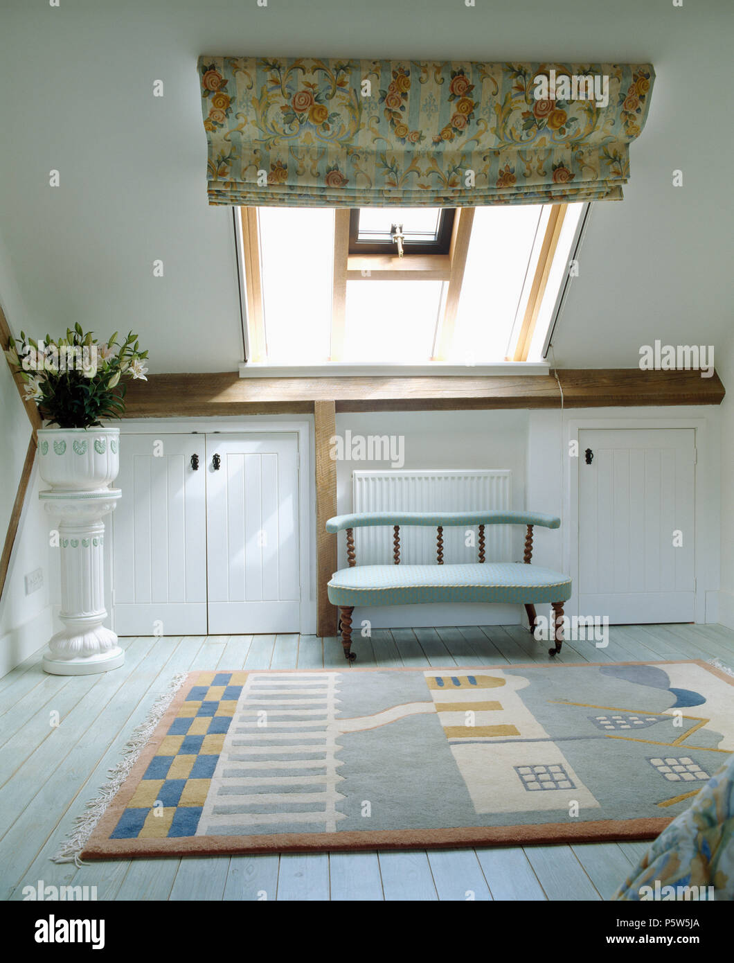 Small sofa below Velux window with floral blind in loft conversion bedroom with patterned rug on white floorboards Stock Photo