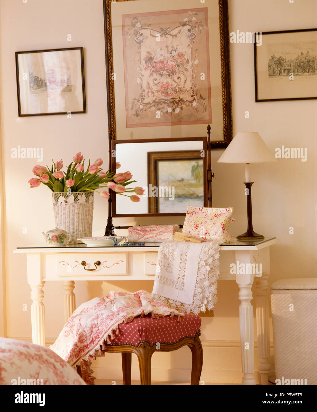 Floral Picture Above Cream Dressing Table With Antique Mirror Between Cream  Lamp And Vase Of Tulips In Traditional Bedroom