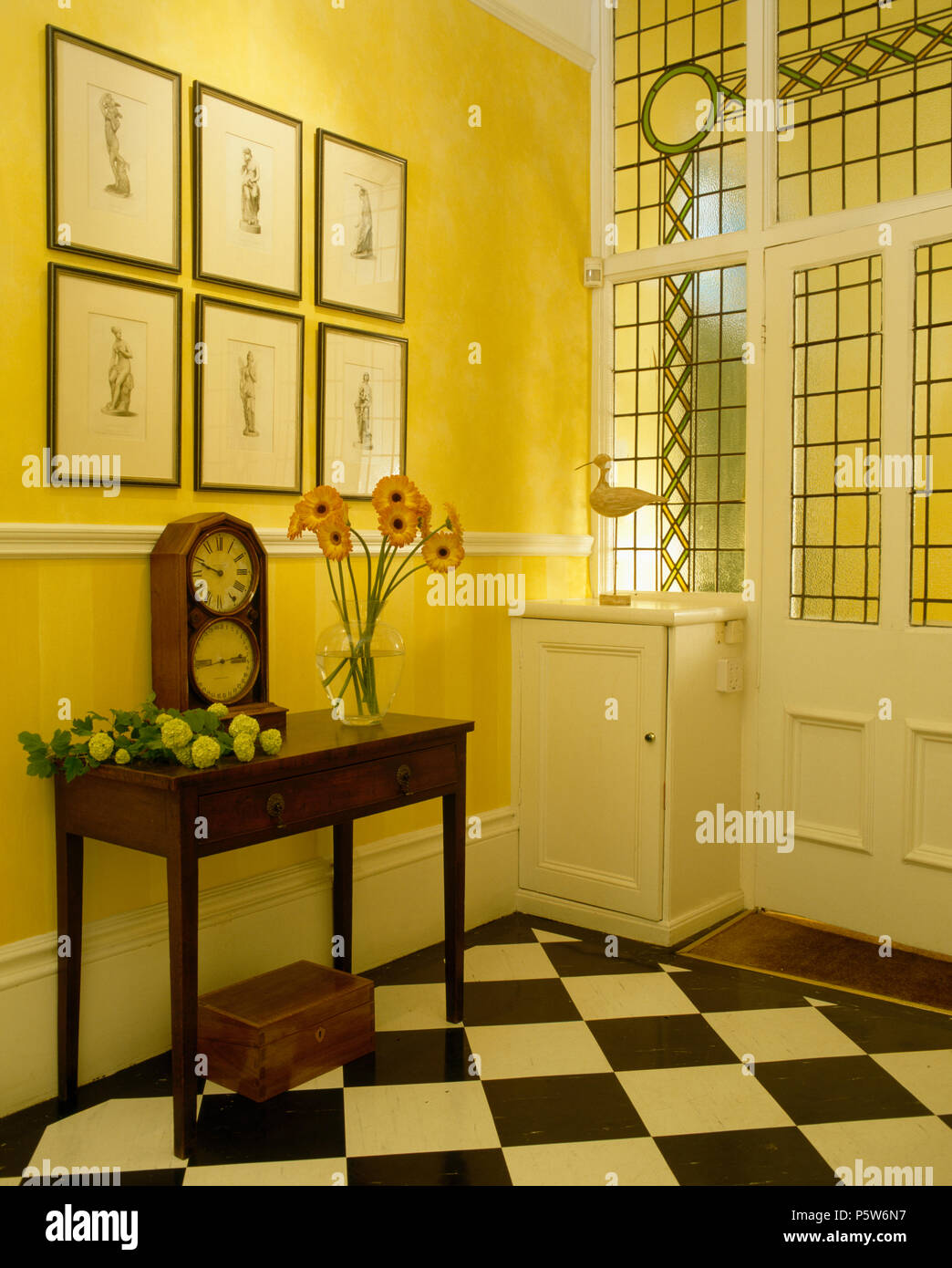 Black+hite cheque-board flooring and vintage console in yelllow hall with opaque glass panels in front door - Stock Image
