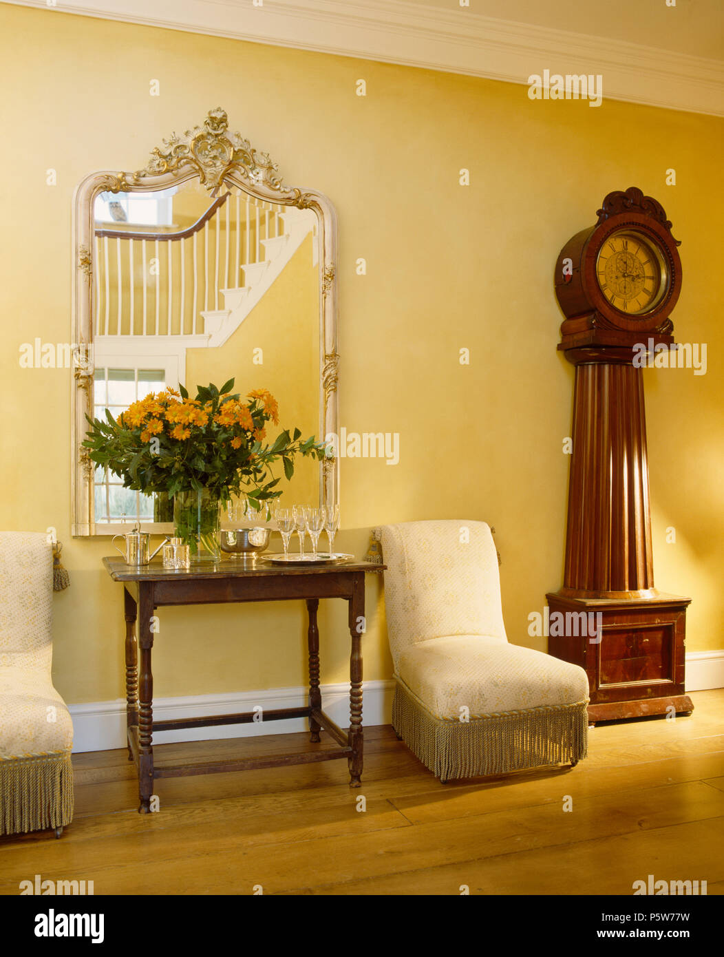 Ornate mirror above console table in country hall with antique long-case clock and upholstered cream chairs - Stock Image