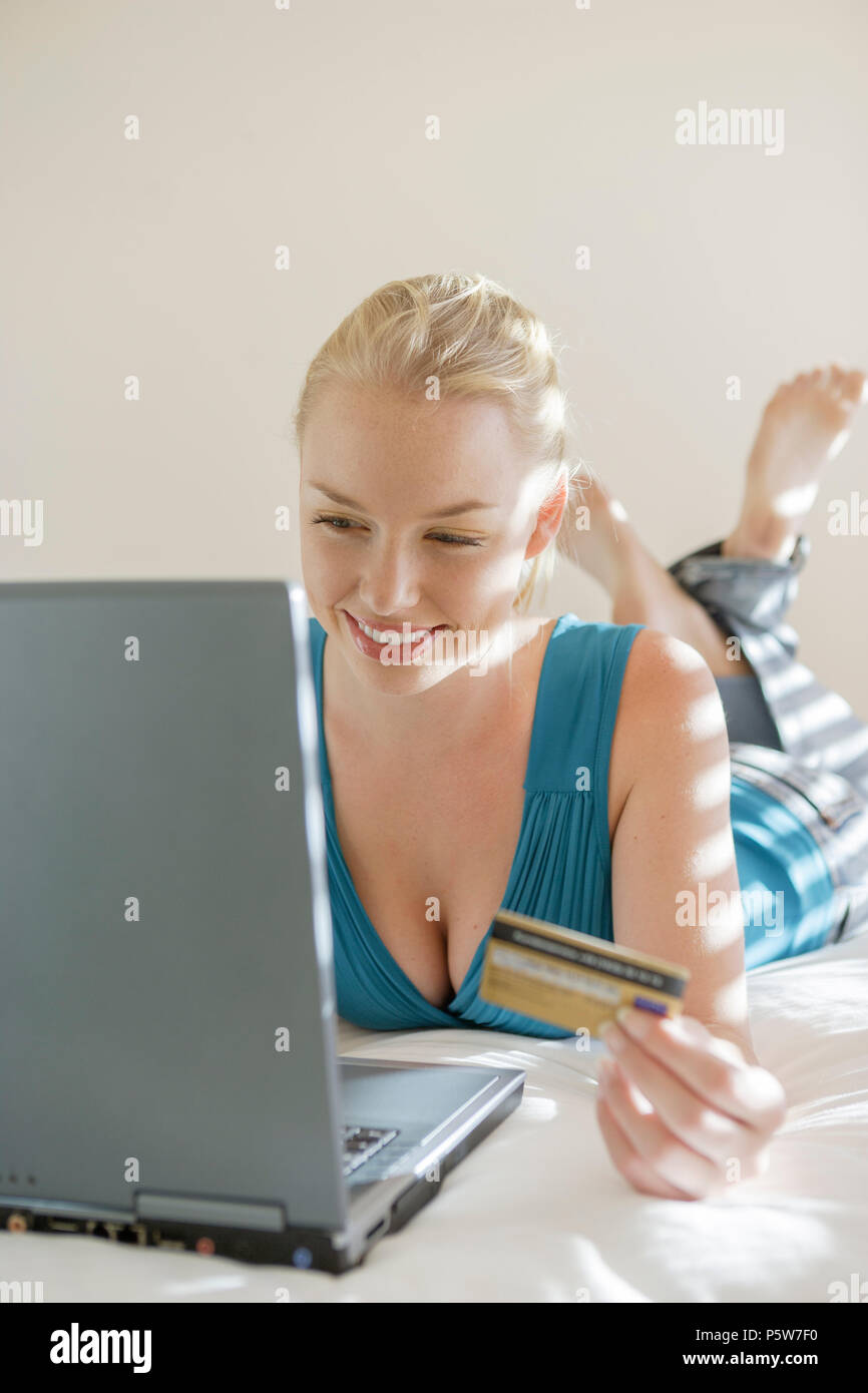 Young woman lying on bed with laptop and creditcard Stock Photo