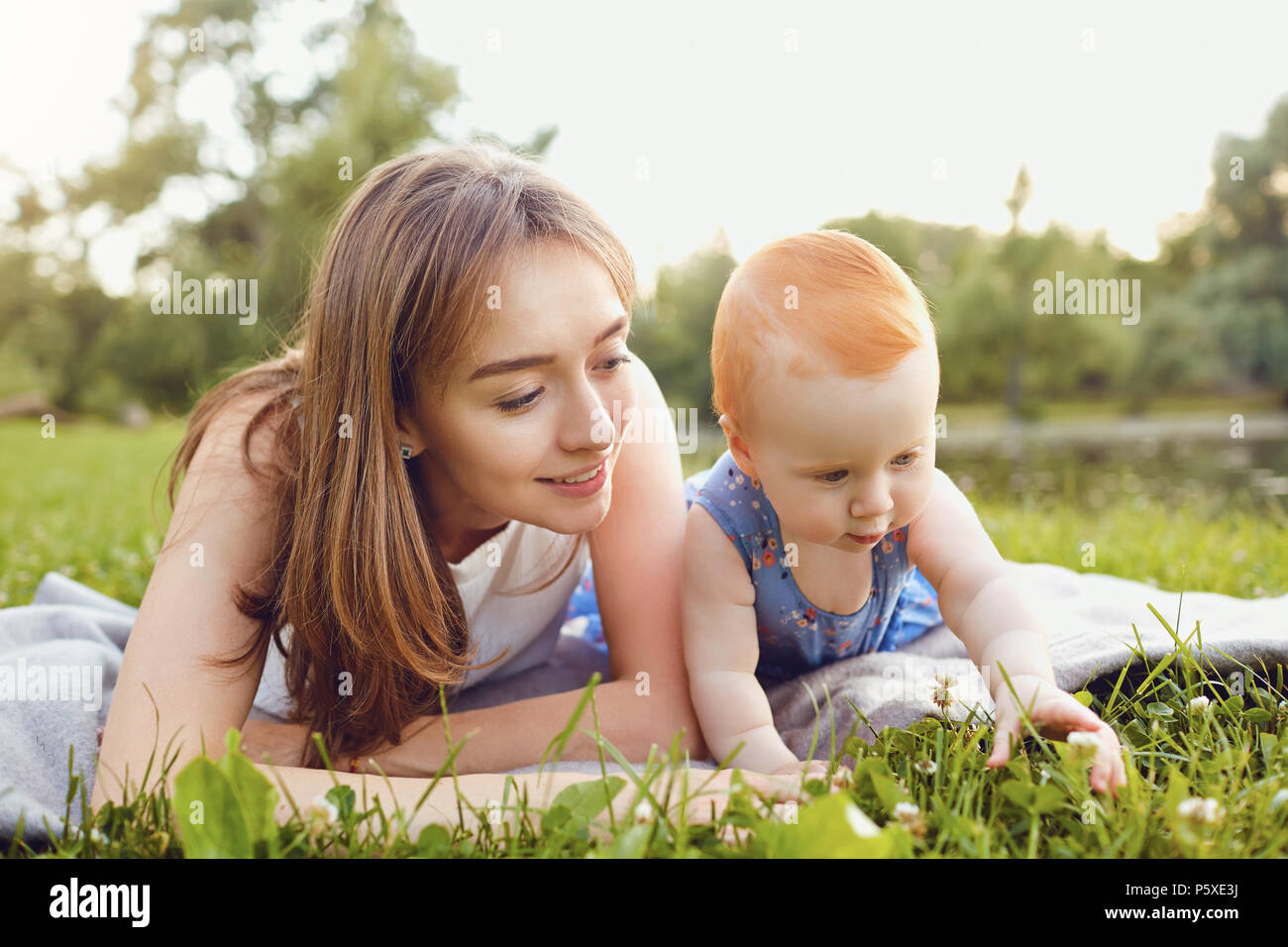 Mother and baby playing on grass in park. - Stock Image