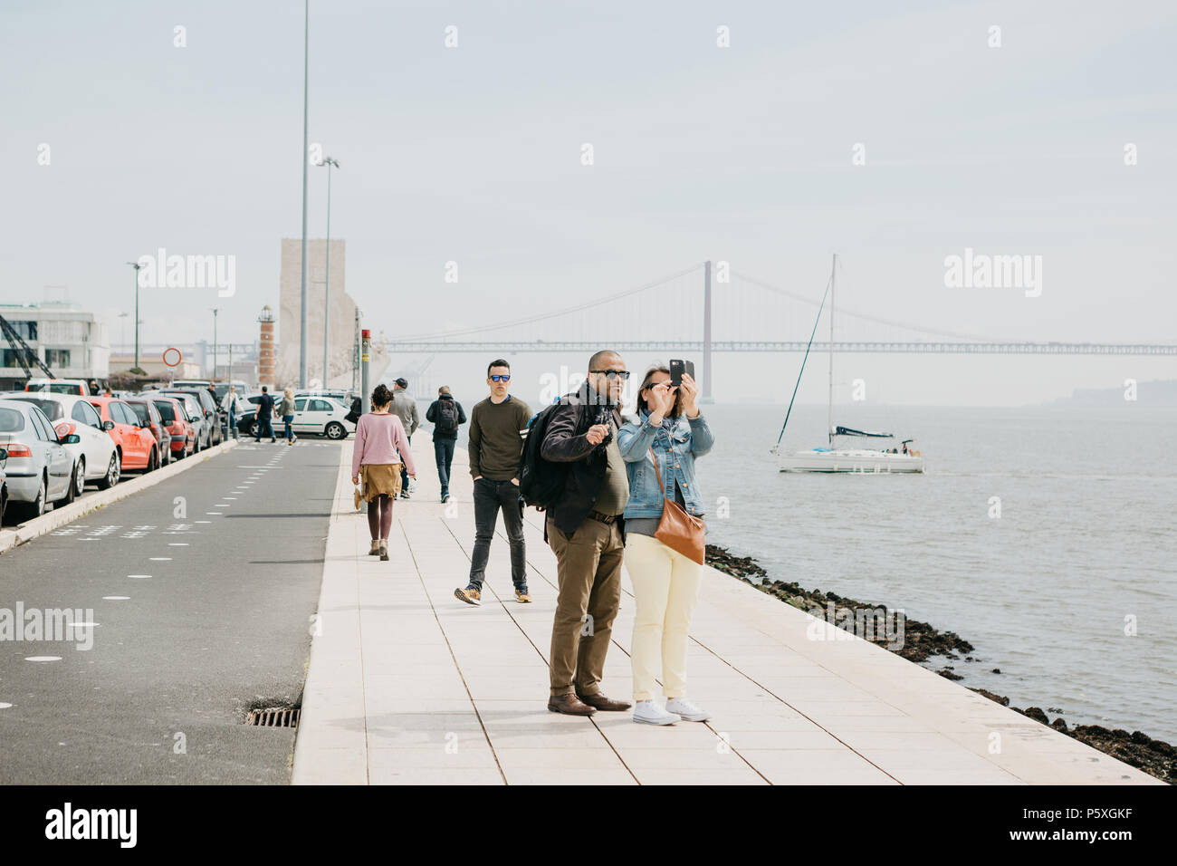 Lisbon, May 1, 2018: A couple of men and women make a selfie on the waterfront in Belem. People are walking around. In the background April 25 The bridge, the sea and the yacht are floating - Stock Image