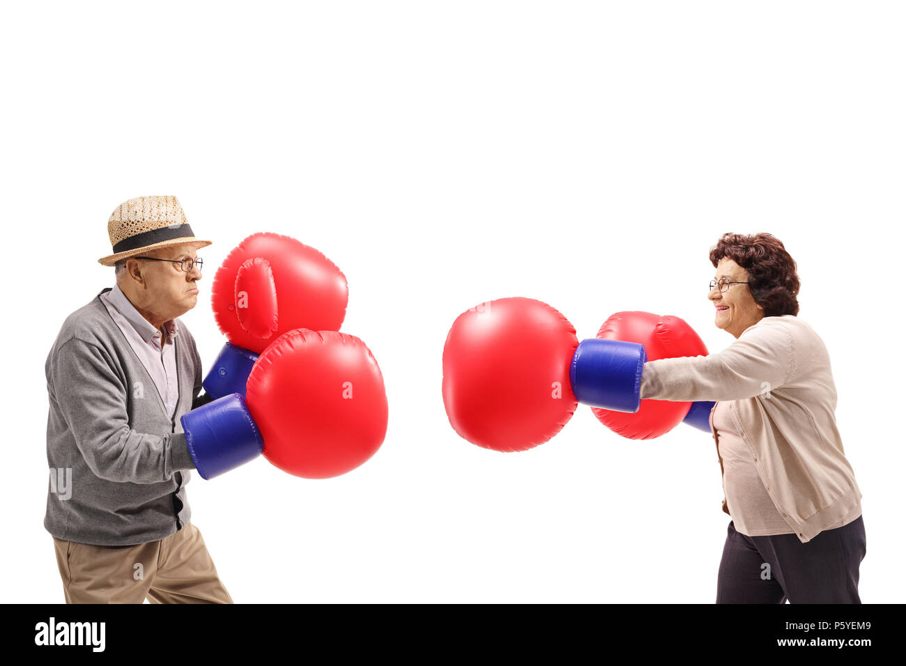 Elderly man and an elderly woman fighting each other with big boxing gloves isolated on white background - Stock Image