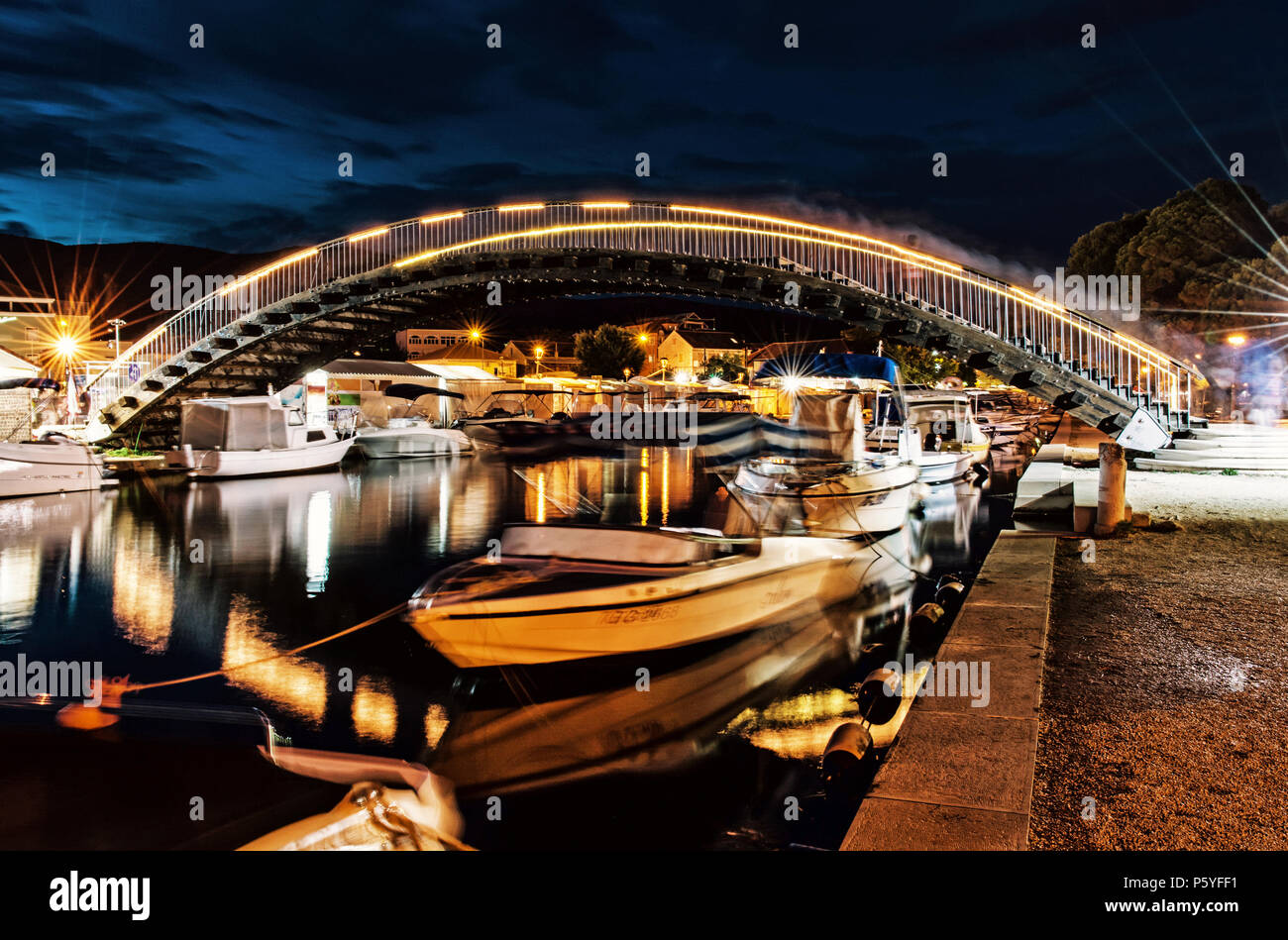 Arched bridge for pedestrians in Trogir, Croatia, Unesco. Night scene. Travel destination. Boats in the port. Yellow photo filter. Stock Photo