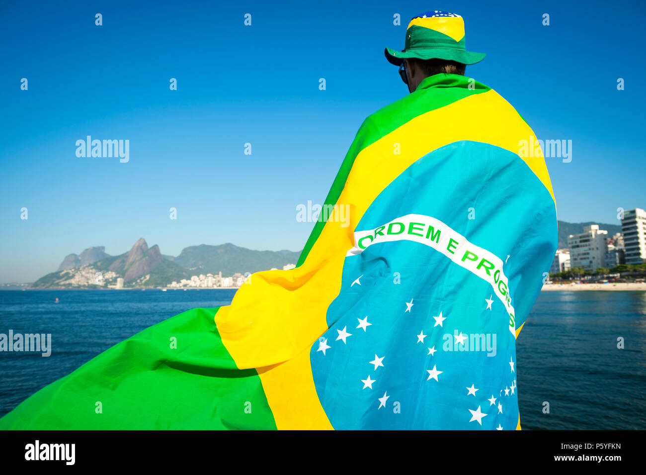 Brazilian football fan wrapped in giant flag and hat in front of Ipanema  Beach city skyline Rio de Janeiro. 9a7388eb00a