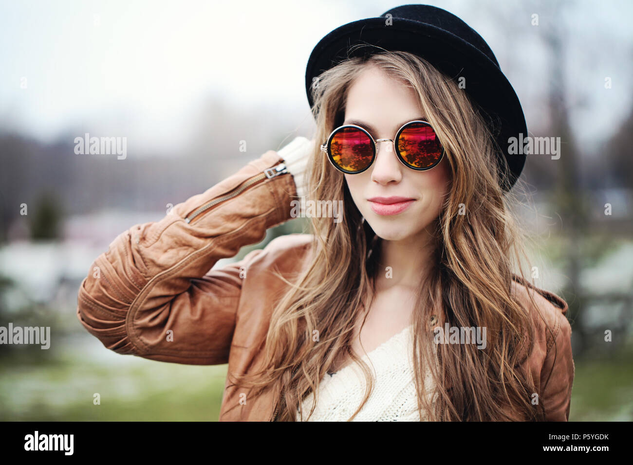 bf625025e5b Young happy woman with long brown hair in sunglasses and black hat ...