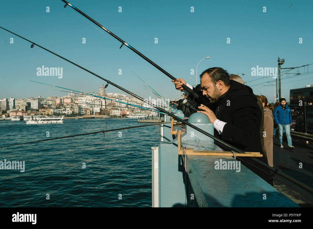 Istanbul, Turkey - January 06, 2018: Local fishermen fishing on Galata Bridge to relax and enjoy their hobby in Istanbul, Turkey. Stock Photo