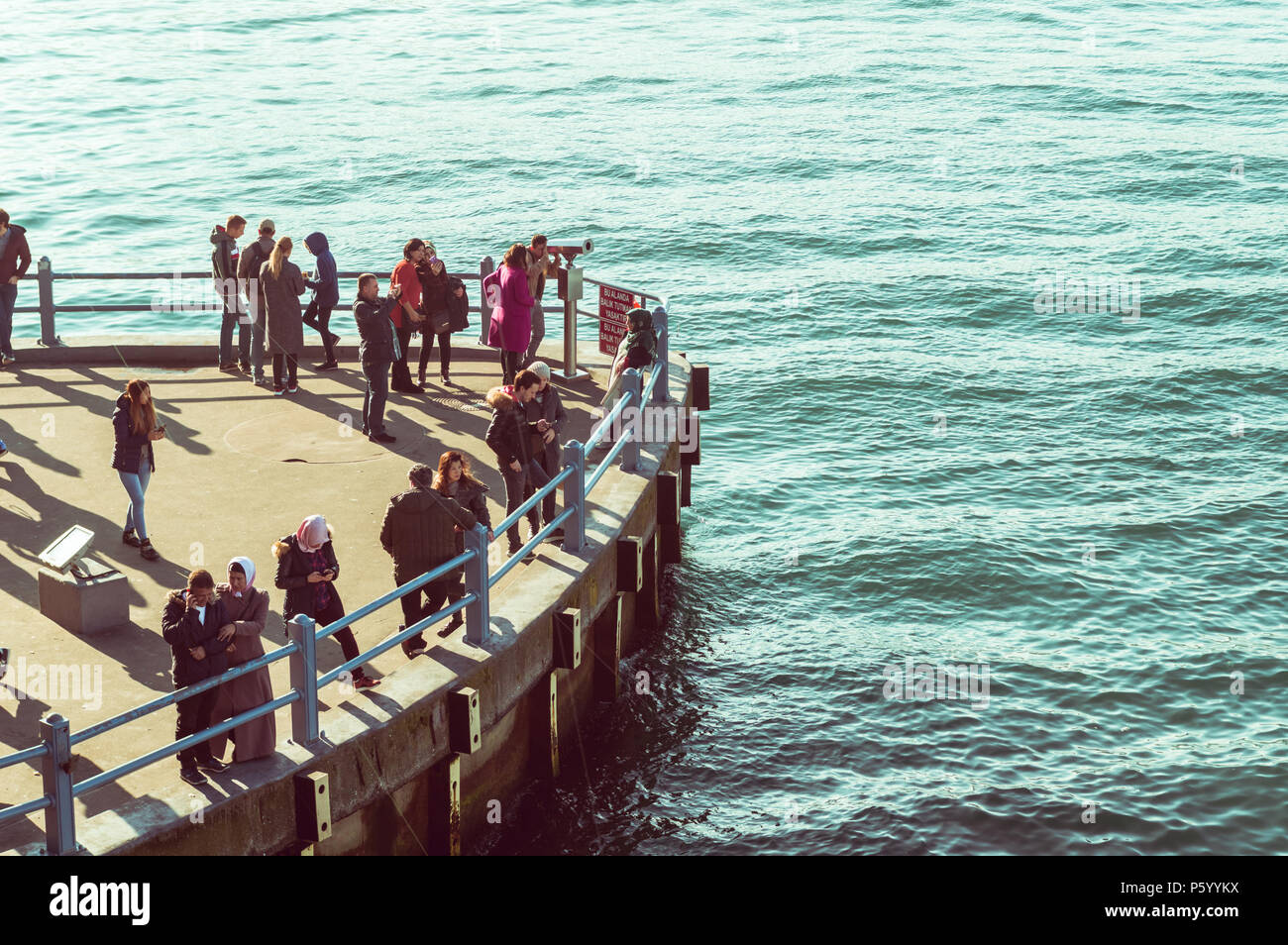 Istanbul, Turkey - January 06, 2018: People viewing seascape on the pier near Galata Bridge in Istanbul, Turkey. Stock Photo