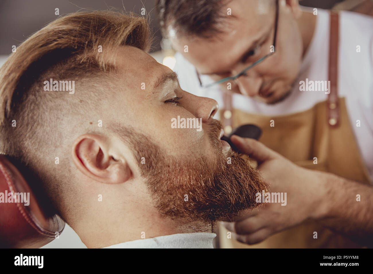 Man in the process of trimming a beard in a barbershop.  Photo in vintage style - Stock Image
