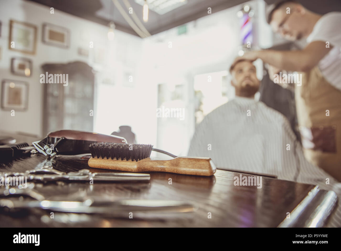 Accesories for cutting on the table in a barbershop and a hairdresser works in the background.  Photo in vintage style - Stock Image