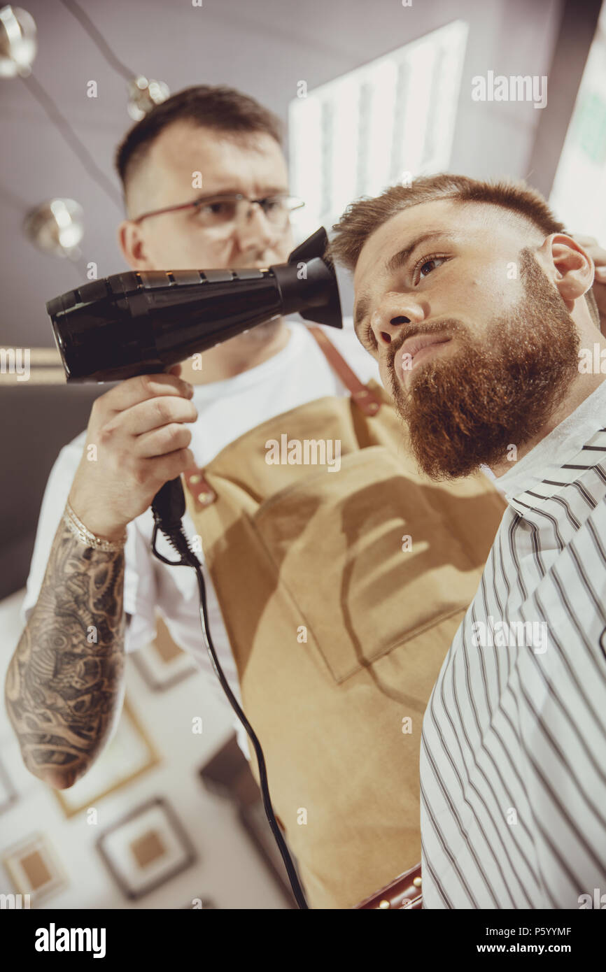 Male hairdresser dries hair of his client. Photo in vintage style - Stock Image