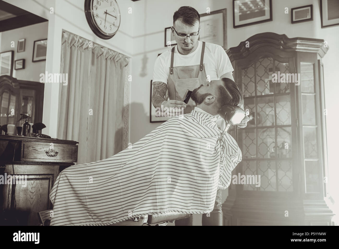 Barber during work in his barber shop. Picture in black and white stylization - Stock Image