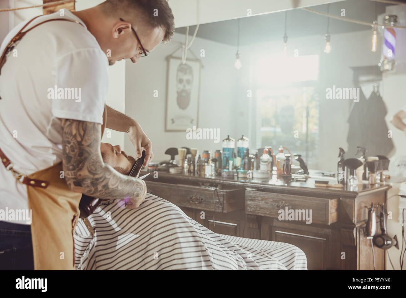 Barber cuts the client's beard in his barber shop. Photo in vintage style - Stock Image