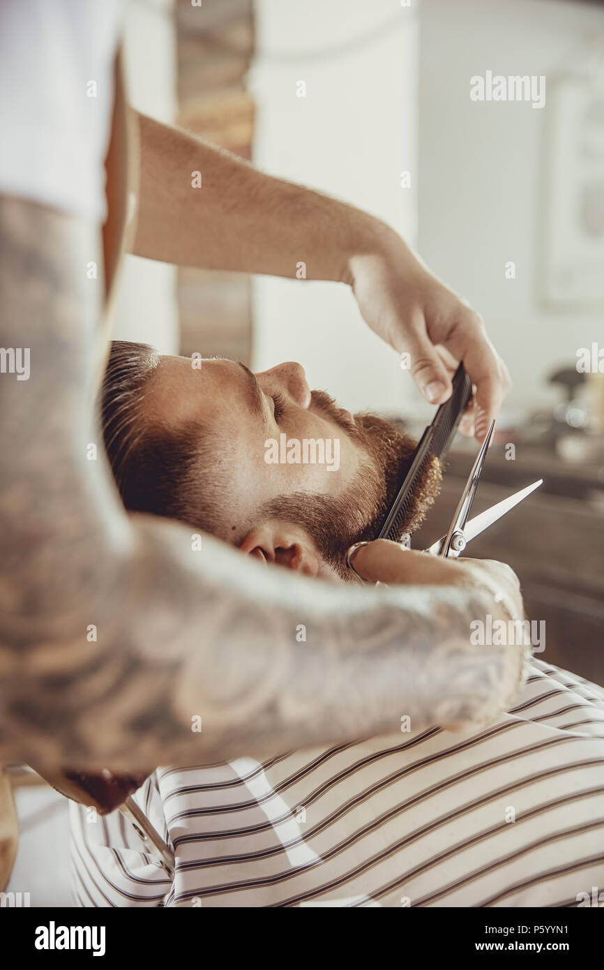 Barber cuts the client's beard with scissors and a comb. Photo in vintage style - Stock Image