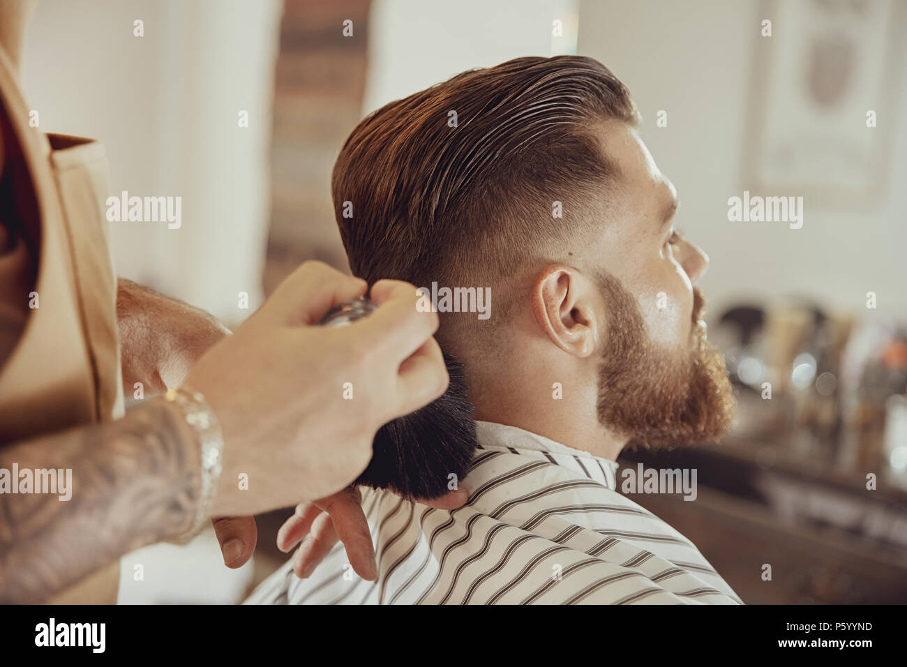 Barber shakes hair off from the client's neck.  Photo in vintage style - Stock Image