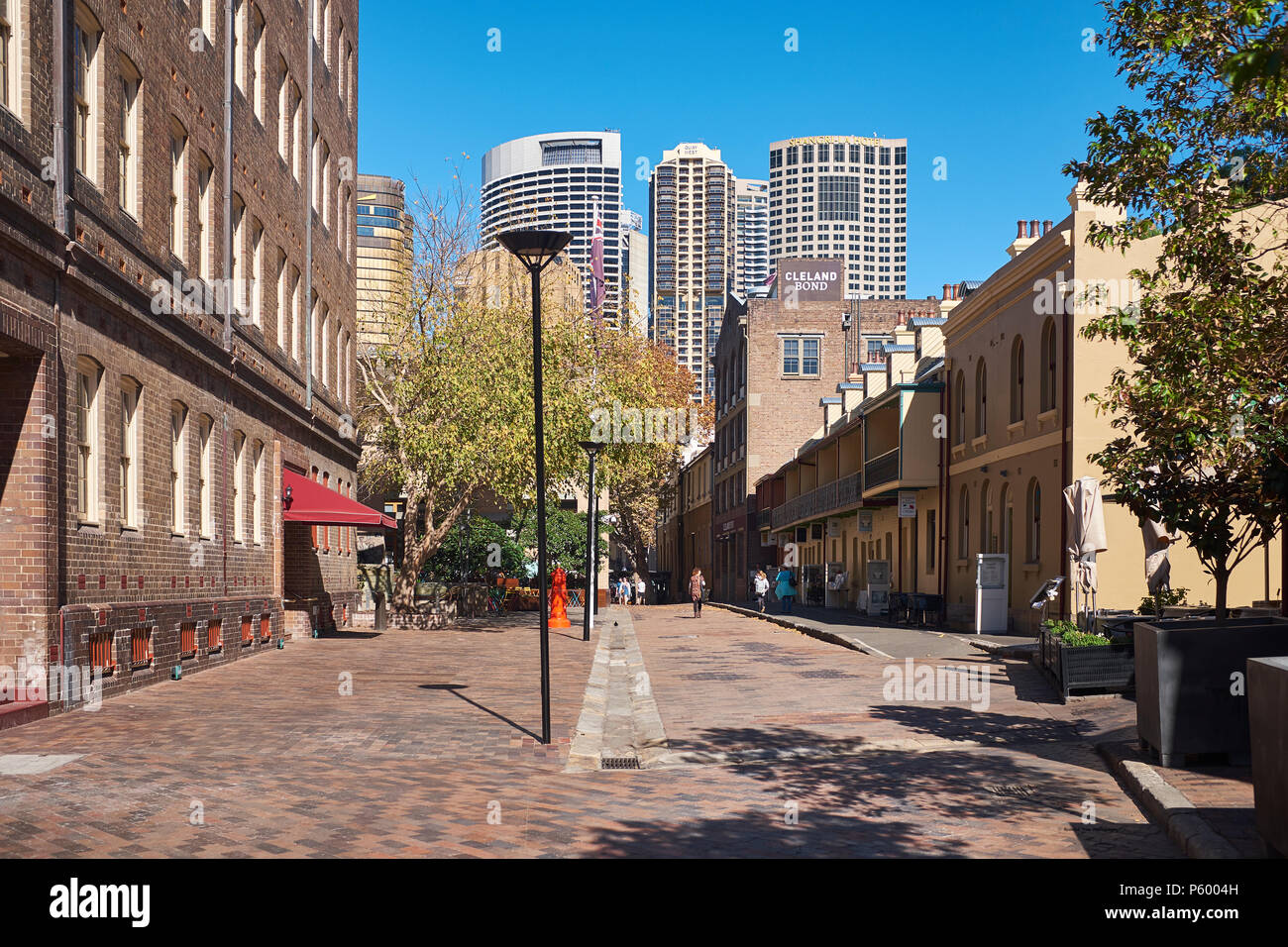 A street view of Playfair Street in The Rocks area of Sydney with modern high-rise buildings of Sydney behind on a sunny and cloudless blue sky day - Stock Image