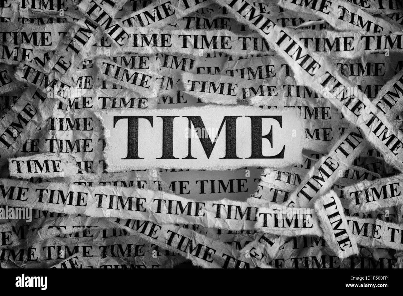 Time. Torn pieces of paper with the words Time. Concept Image. Black and White. Closeup. - Stock Image