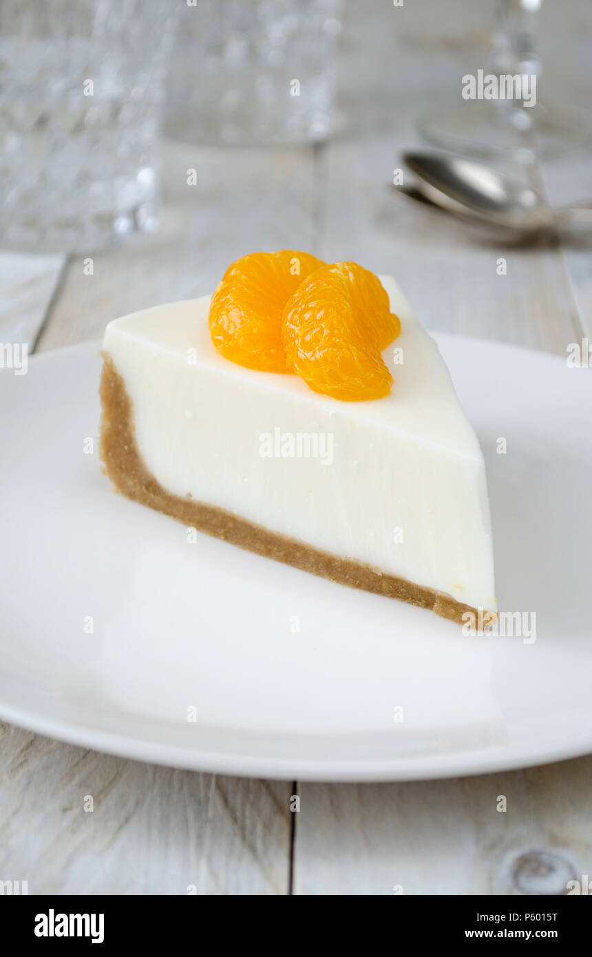 Cheesecake with slices of mandarin on white plate - Stock Image