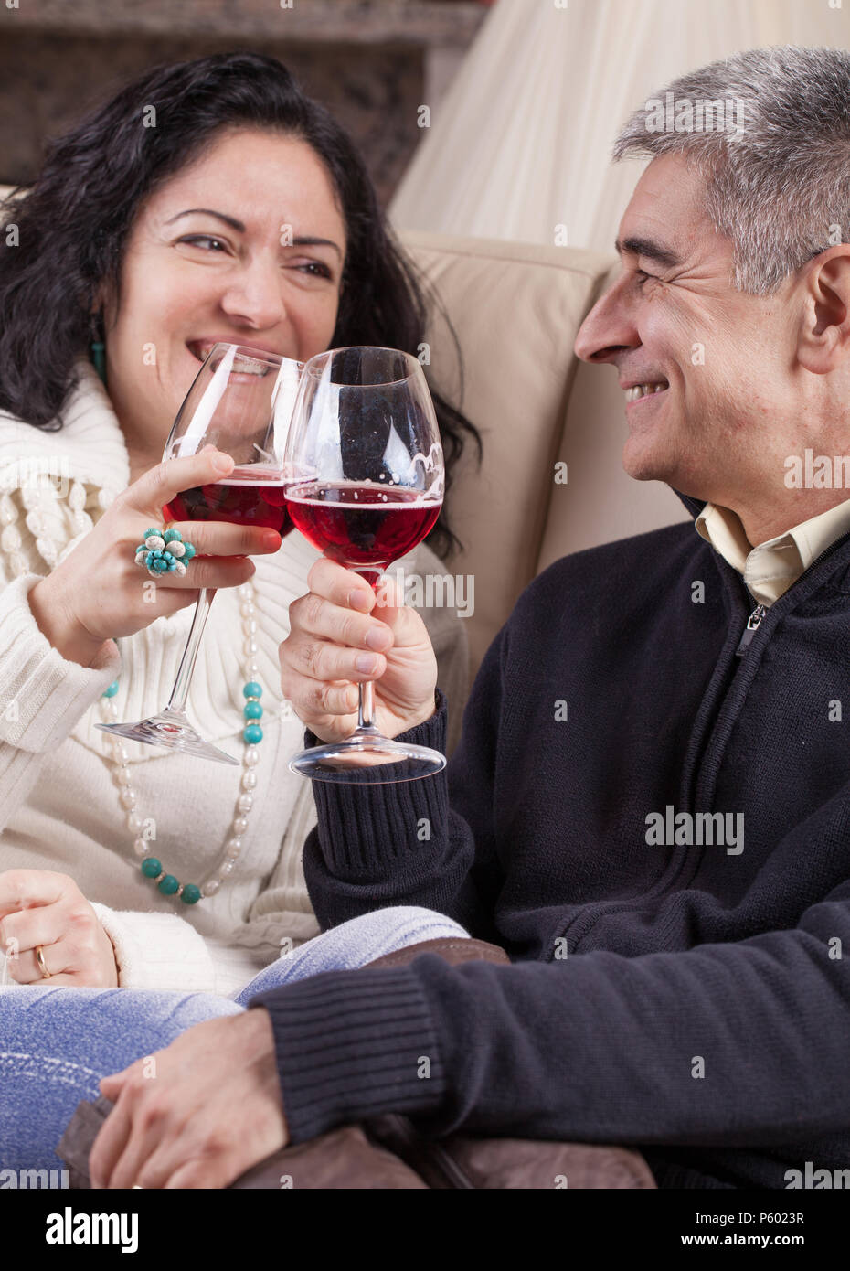 Middle aged Caucasian heterosexual couple relaxed, drinking red wine. - Stock Image