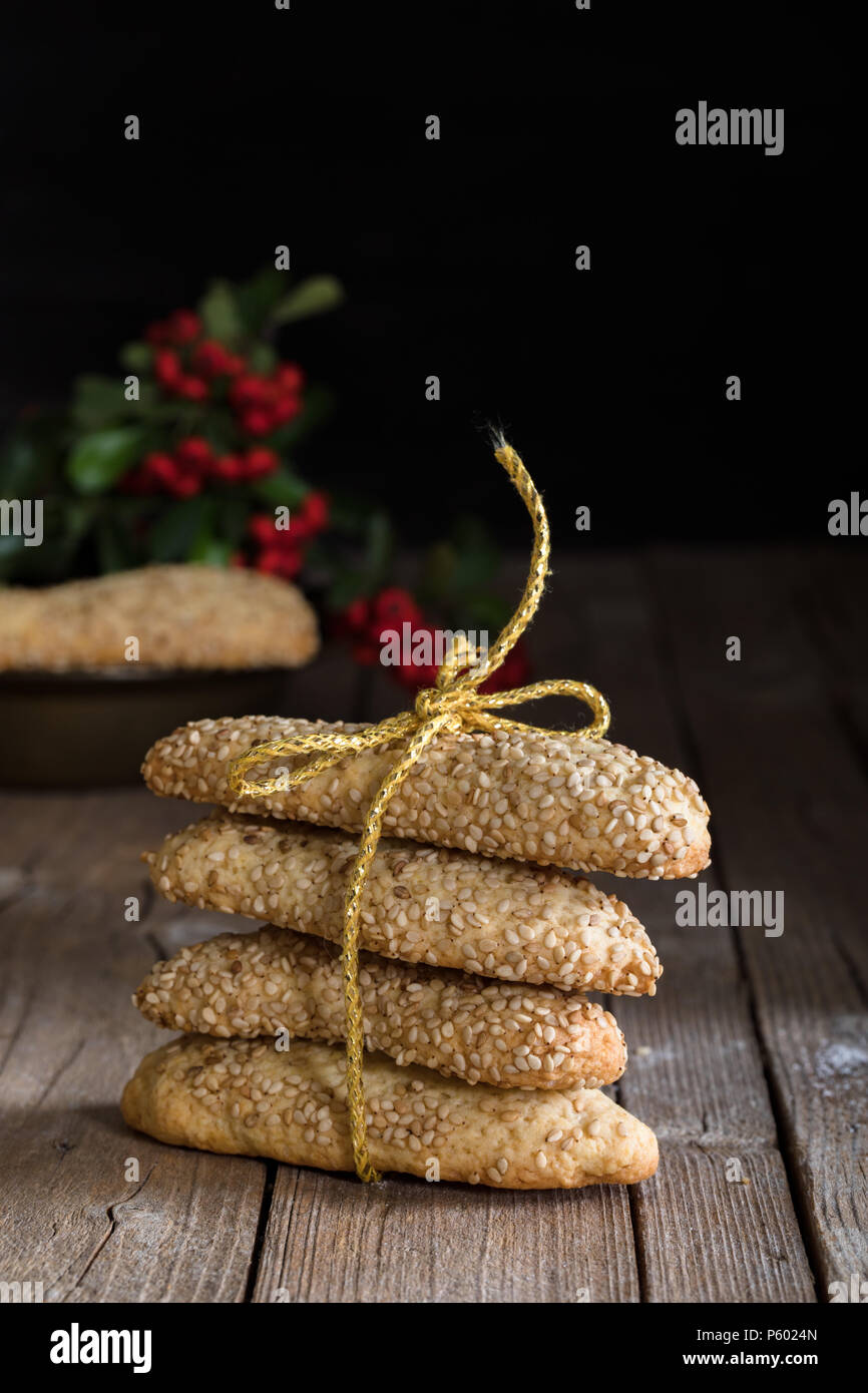 Sicilian biscuits with sesame seeds tight with golden bow and decorated with red berries for winter holidays. - Stock Image