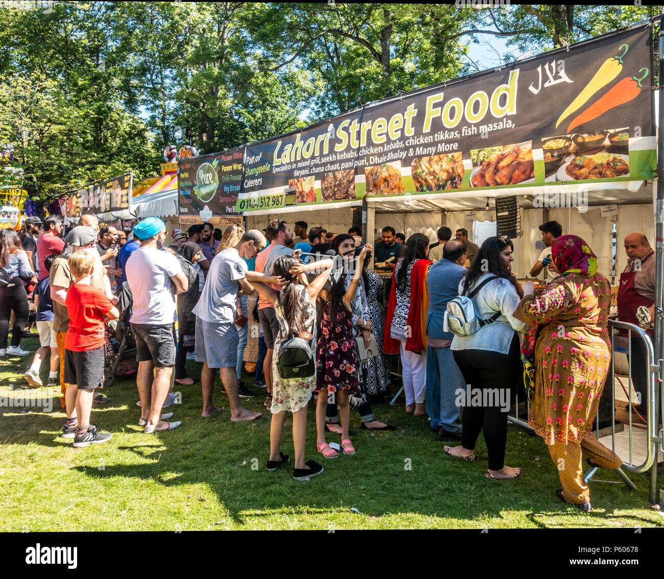 Multi-ethnic crowd queueing to buy a meal from the Lahore Street Food stall at Glasgow Mela, 2018, in Kelvingrove Park in the city's West End - Stock Image