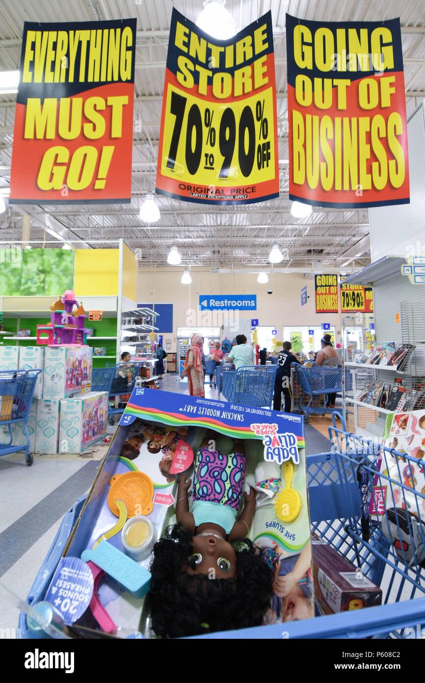 Unsold toys sit in a shopping cart below 'going out of business' signs at a Toys R Us store in Manchester, N.H., USA, July 25, 2018. - Stock Image