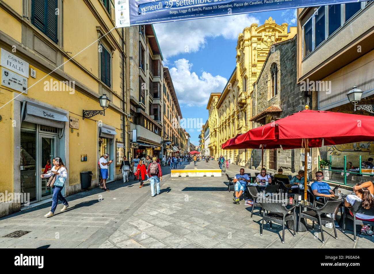 Tourists and locals enjoy a sunny day on the Corso Italia, the main shopping and dining street through the Tuscan city of Pisa, Italy - Stock Photo
