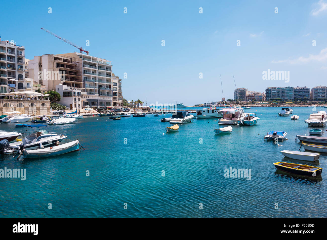 Rowing boats, yachts and cabin cruisers in Spinola Bay, St. Julian's, Malta - Stock Image