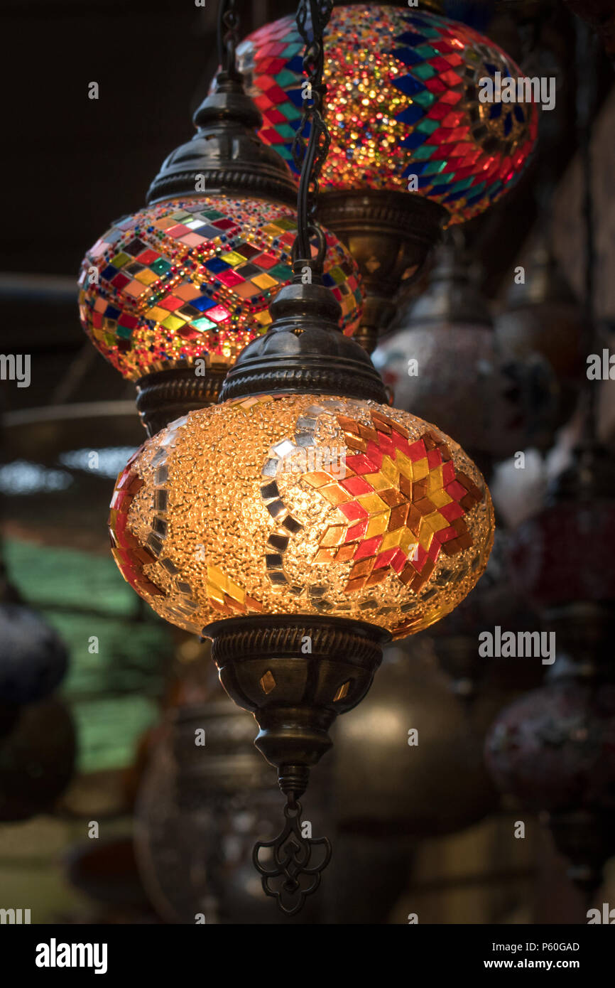 Colourful patterned lamps, in the traditional Moroccan design, hang from a stall in a Marrakech souk. The lamps are lit up. Stock Photo
