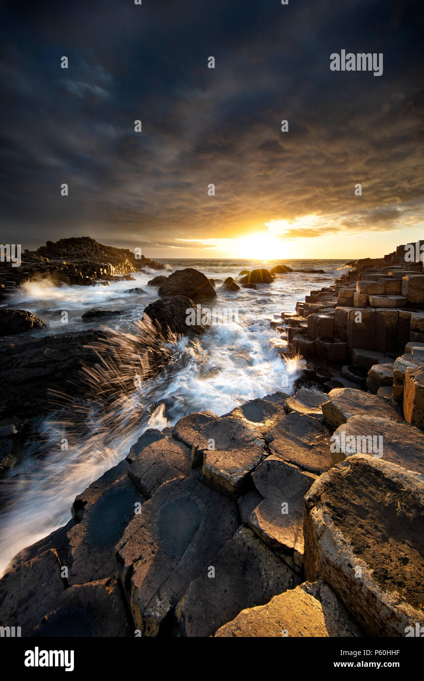 Waves crashing into Giant's Causeway at Sunset - Stock Image