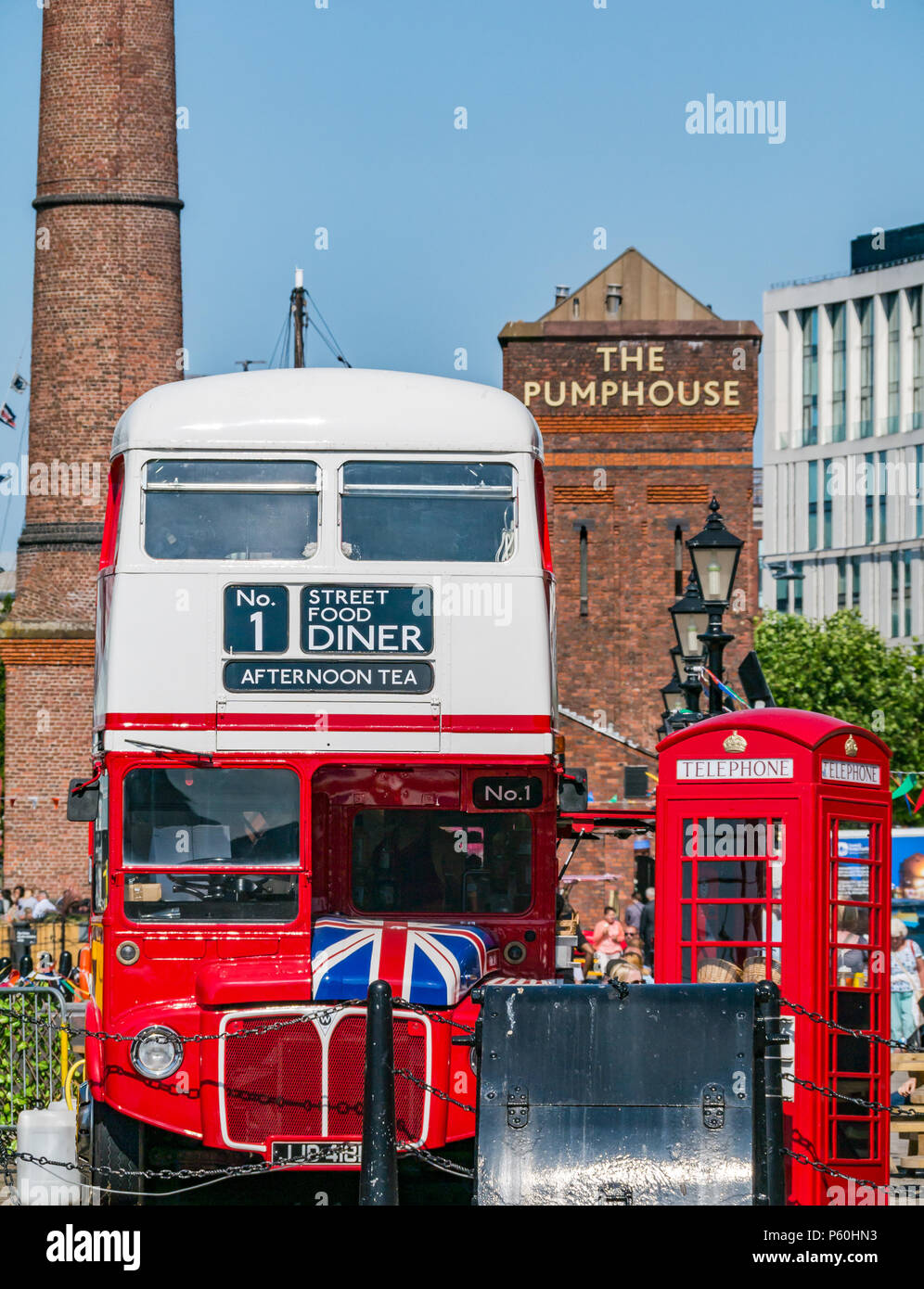 Traditional red London bus and British red telephone box, Albert Dock, Liverpool, England, UK with brick Pumphouse pub and brick tower in background - Stock Image