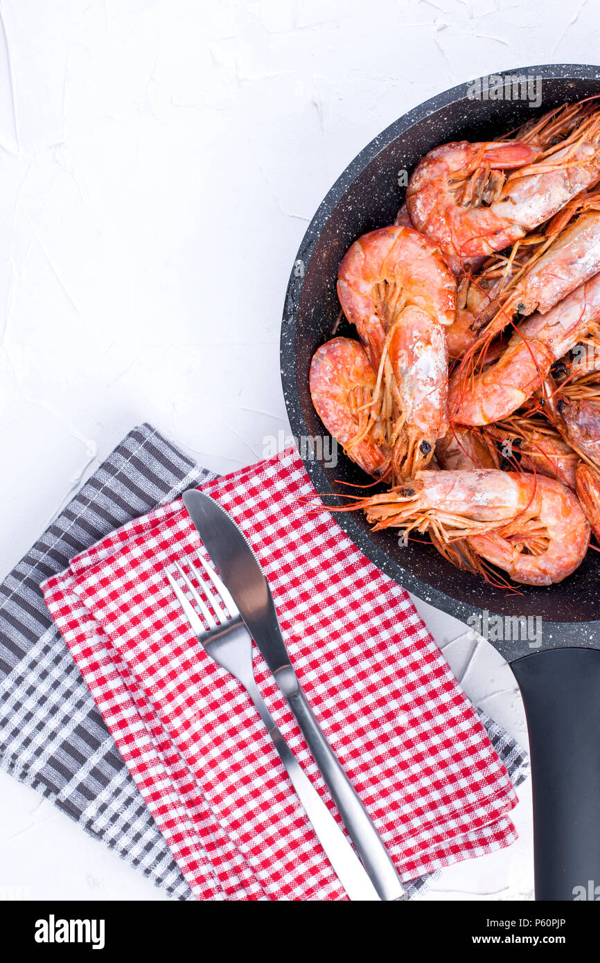 Large shrimps fried in a frying pan. On a white table and a table towel. Lunch from seafood. Free space for text. Copy space - Stock Image