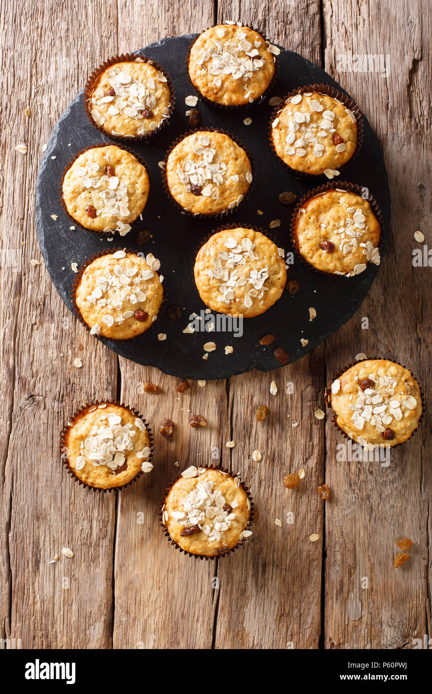 Homemade muffins of oatmeal with raisins close-up on the table. vertical top view from above, rustic style - Stock Image
