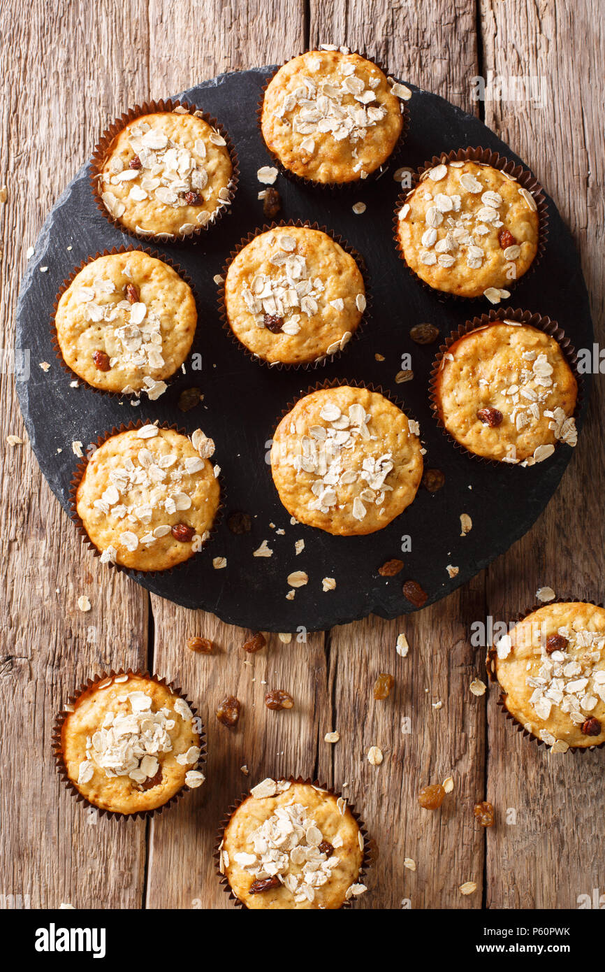 Low-calorie muffins of oatmeal with raisins and honey close-up on the table. vertical top view from above - Stock Image