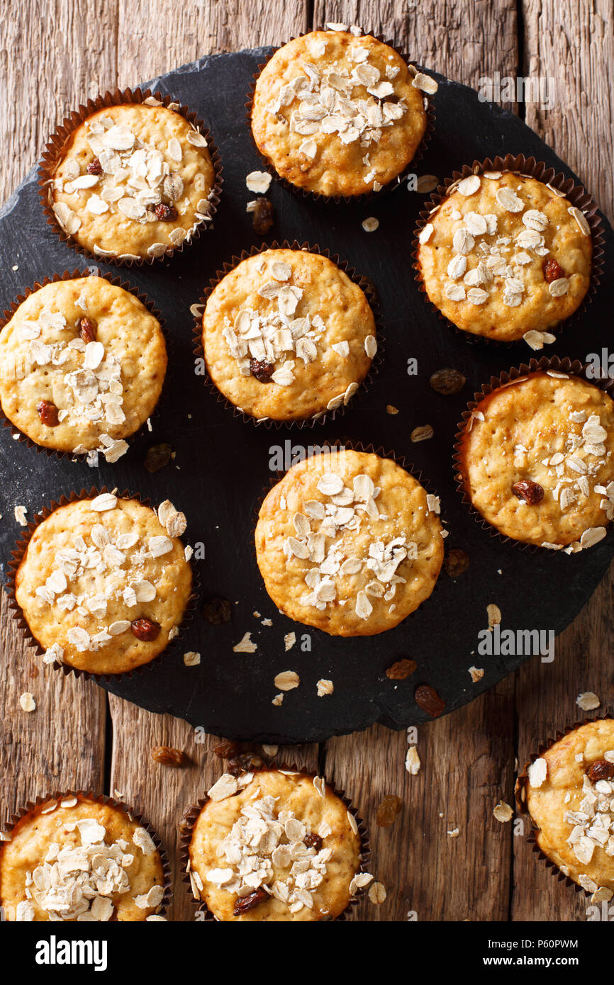 Dietary muffins from oat flakes with raisins and honey close-up on the table. vertical top view from above - Stock Image