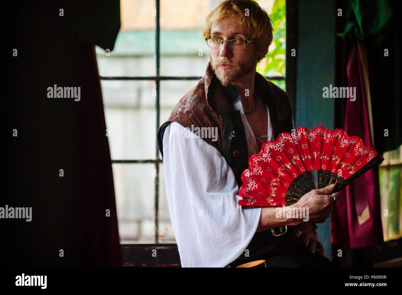A Renaissance actor sits at a window with a red fan. - Stock Image