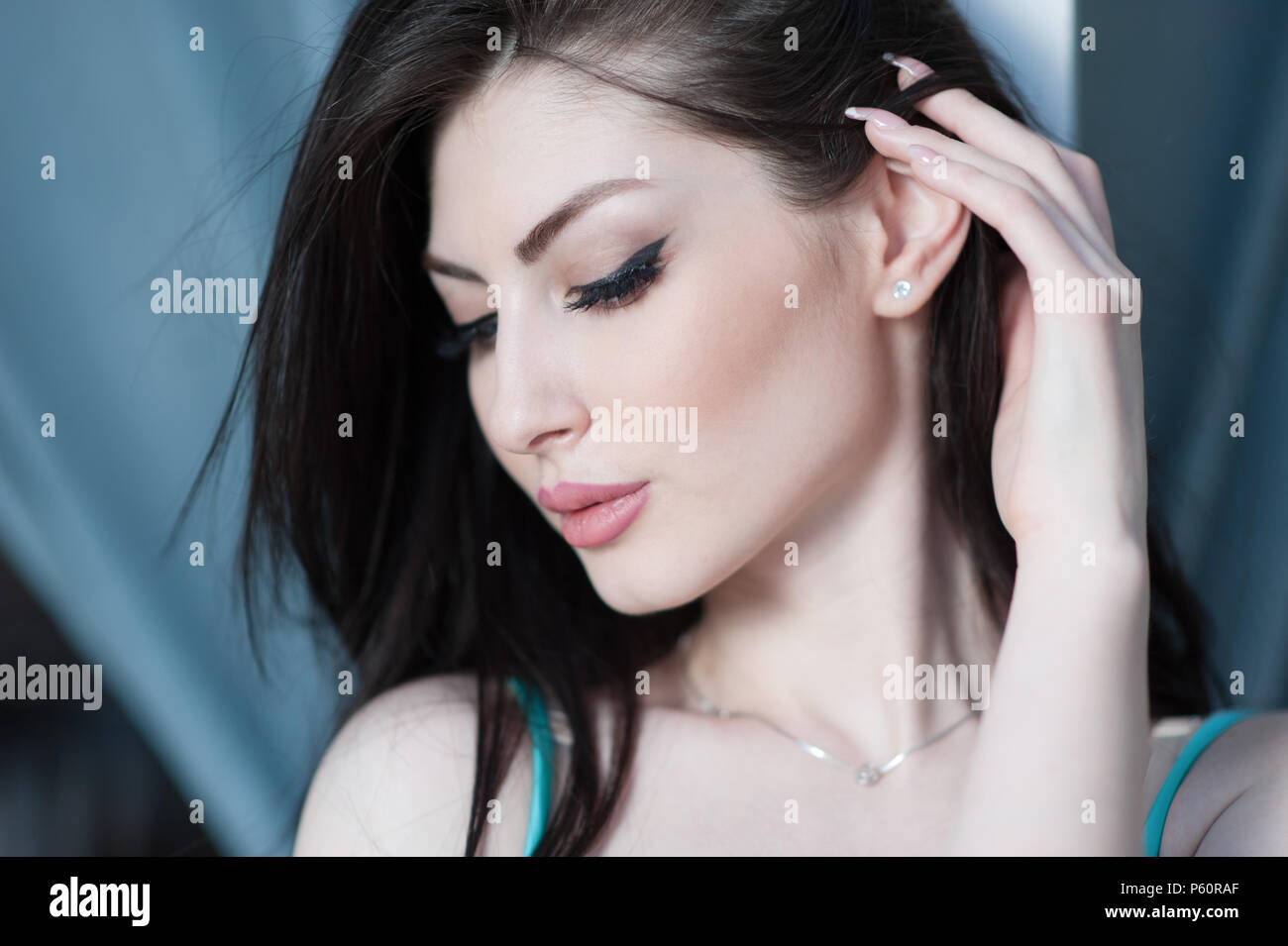 Cute Young Caucasian Woman With Closed Eyes Touching Her Hair