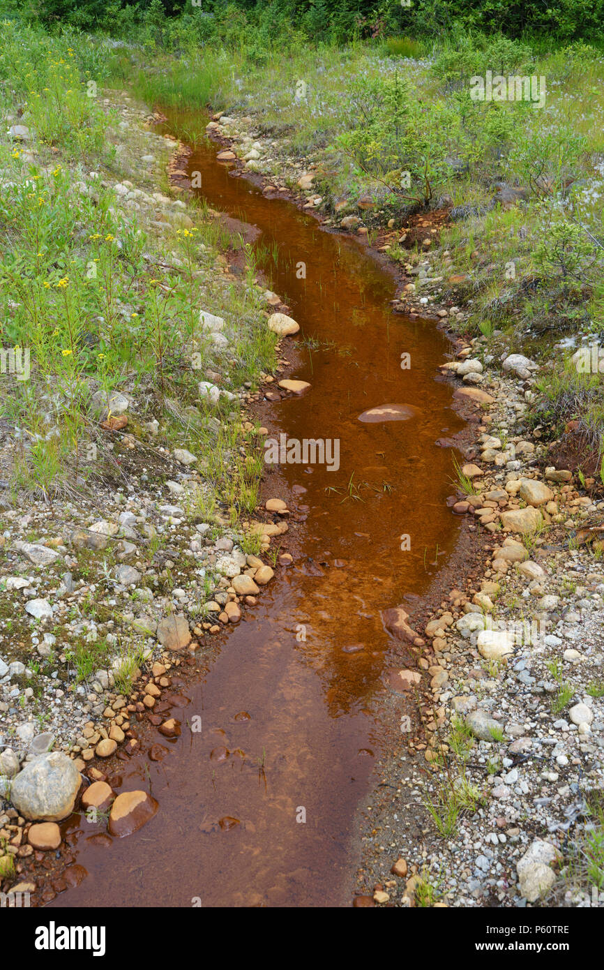 Stream carrying reddish brown water rich in iron deposits. - Stock Image