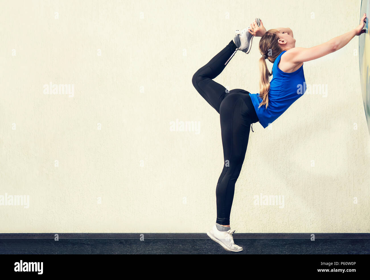 Pretty blonde woman with slim body stand in yoga pose with one leg