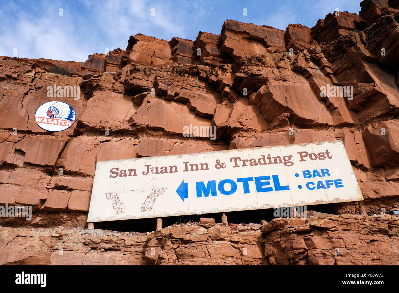 On a red rock cliff near Mexican Hat, Utah, advertising signs for Wasatch Oil and Gaz,  and San Juan Inn and Trading Post. - Stock Image
