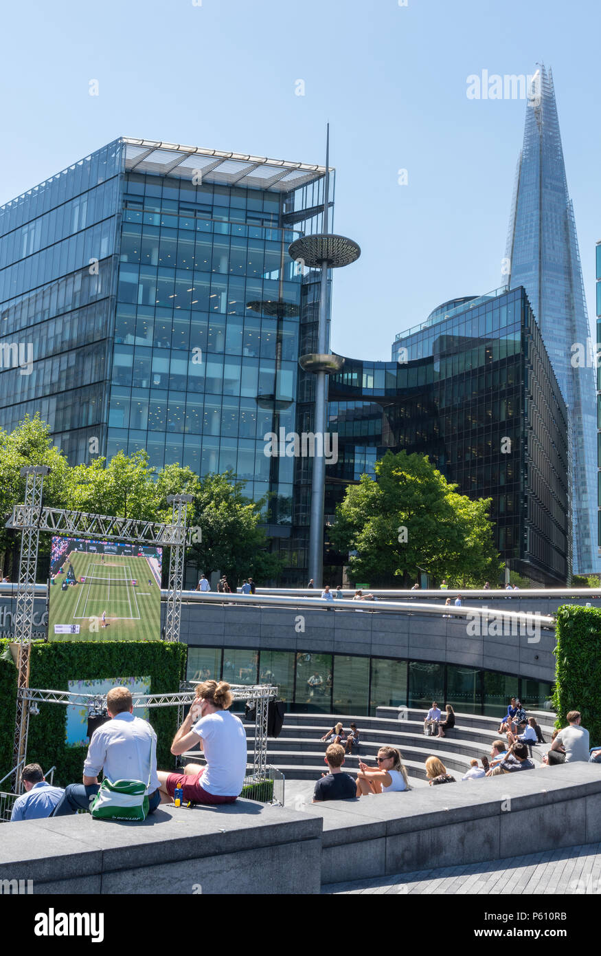 Lond, UK, 27 June 2018. The heatwave continues in central London with clear blue skies and potentially record breaking temperatures. Crowds of tourists and office workers at more london place and Tower bridge enjoying the hot weather and the beautiful sunshine sitting on the grass and sunbathing. Credit: Steve Hawkins Photography/Alamy Live News - Stock Image
