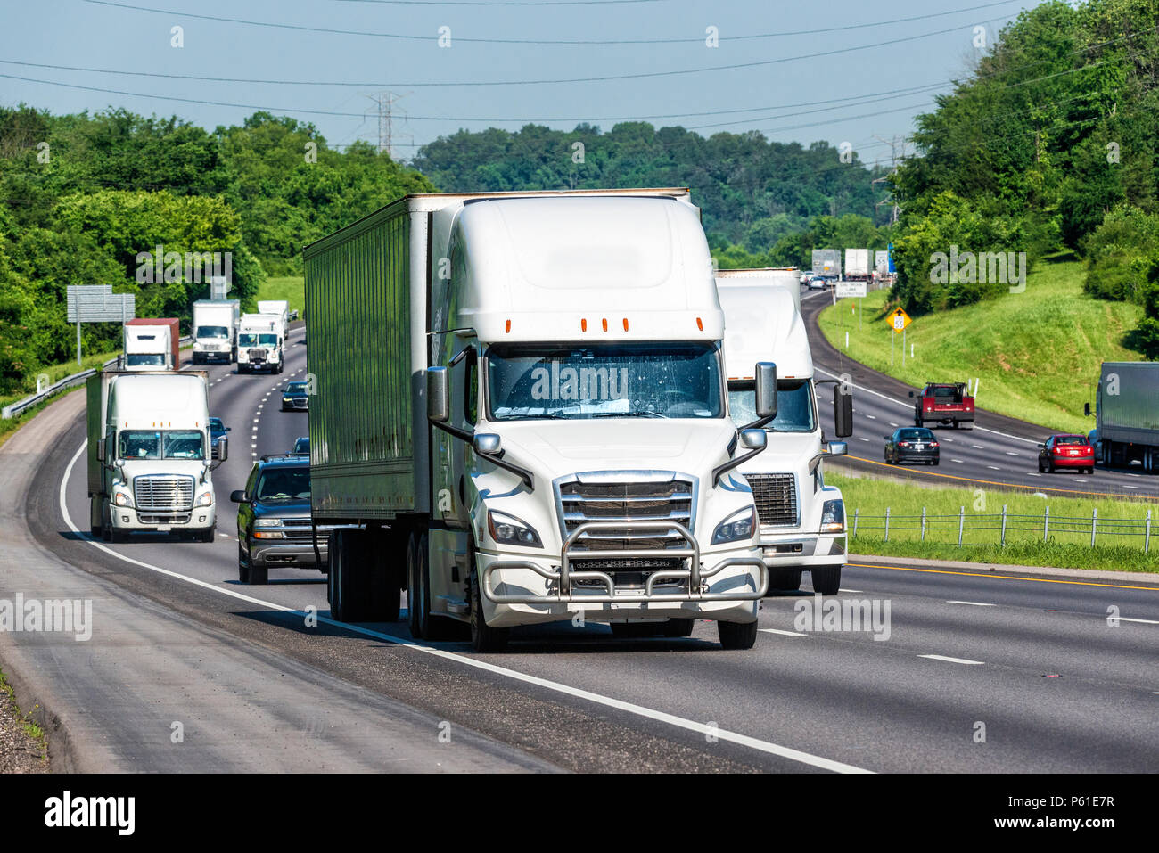 Trucks and personal vehicles navigate a busy interstate. Note: All logos and identifying marks have been removed from all vehicles.  Image was created - Stock Image