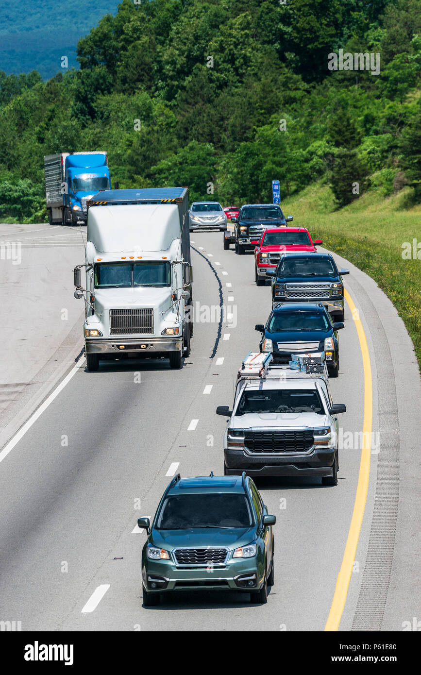 A long line of mixed traffic travels I-40 in east Tennessee. Note: All logos and identifying marks have been removed from all vehicles.  Image was cre - Stock Image