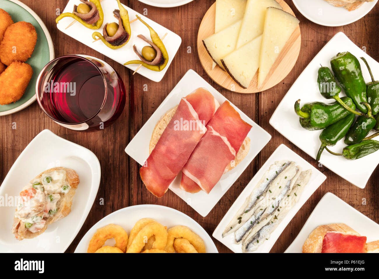 The food of Spain. An overhead closeup photo of various Spanish tapas, shot from above on a dark rustic texture. Jamon, cheese, wine, calamari rings,  - Stock Image