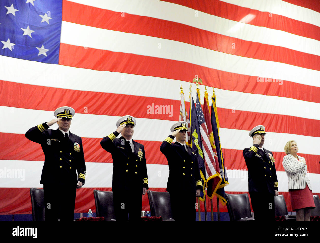 NEWPORT NEWS, Va., (April 8, 2016) The official party honors the national anthem during a change of command ceremony in Pre-Commissioning Unit Gerald R. Ford's (CVN 78) hangar bay.  Ford is the first of a new class of aircraft carriers currently under construction by Huntington Ingalls Newport News Shipbuilding. (U.S. Navy photo by Mass Communication Specialist Seaman Cathrine Mae O. Campbell/Released) - Stock Image
