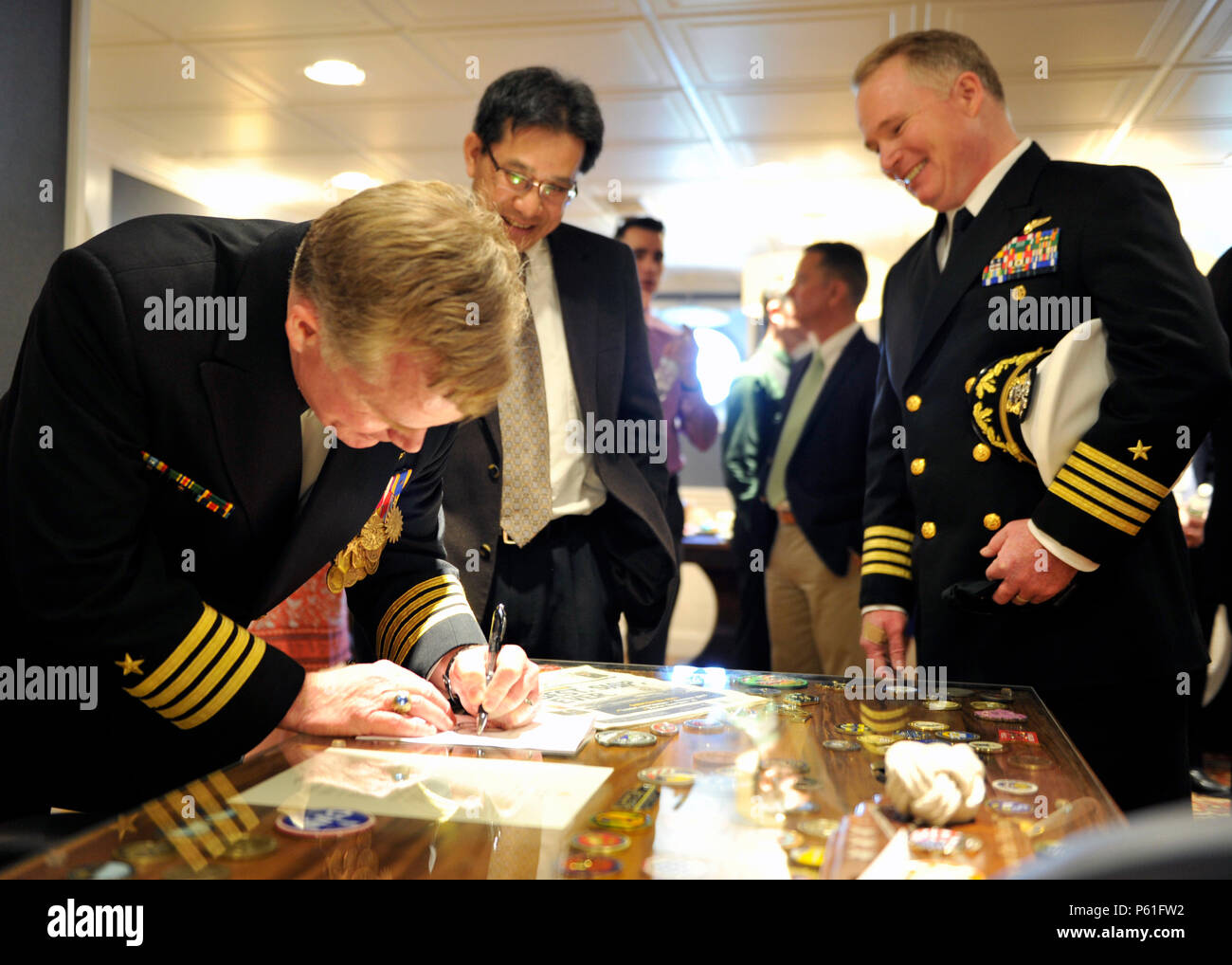160408-N-OG138-081 NEWPORT NEWS, Va., (April 8, 2016) Capt. Richard McCormack signs a program for a distinguished guest before Pre-Commissioning Unit Gerald R. Ford's (CVN 78) change of command in the ship's hanger bay. Ford is the first of a new class of aircraft carriers currently under construction by Huntington Ingalls Newport News Shipbuilding. (U.S. Navy photo by Mass Communication Specialist 3rd Class Matthew R. Fairchild/Released) - Stock Image