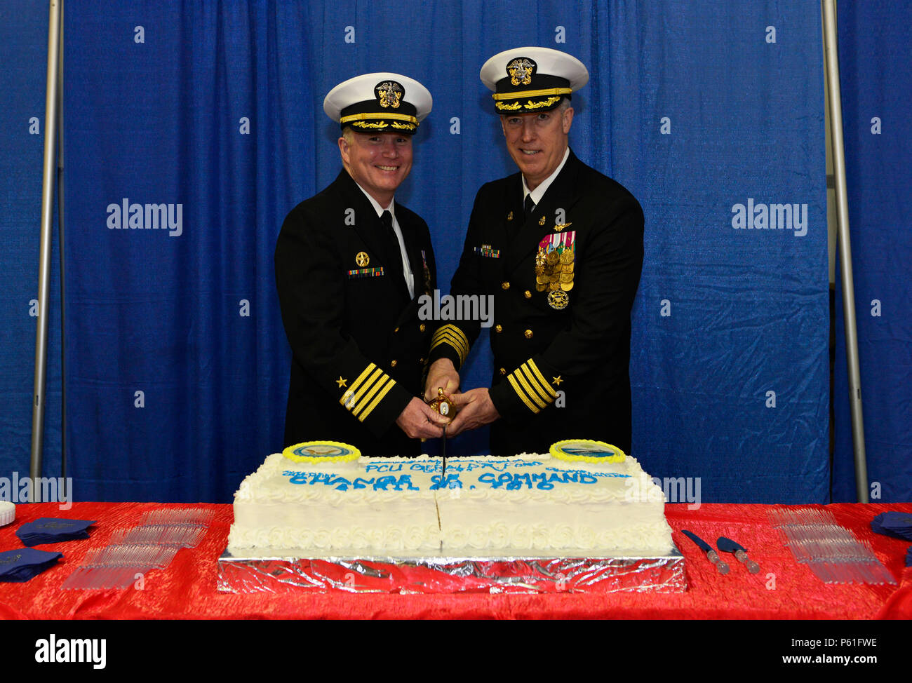 NEWPORT NEWS, Va., (April 8, 2016) -- Capt. Richard McCormack, commanding officer of Pre-Commissioning Unit Gerald R. Ford (CVN 78), and Capt. John F. Meier cut the cake at a reception following a change of command in the ship's hangar bay. Ford is the first of a new class of aircraft carriers currently under construction by Huntington Ingalls Newport News Shipbuilding. (U.S. Navy photo by Mass Communication Specialist Seaman Apprentice Gitte Schirrmacher/Released) - Stock Image