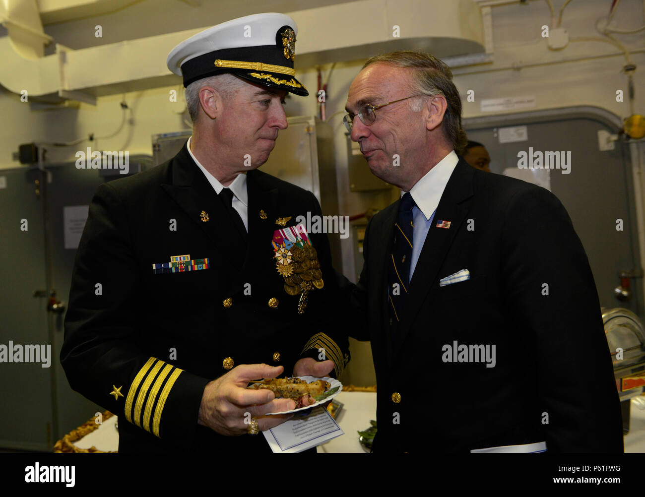 NEWPORT NEWS, Va., (April 8, 2016) -- Capt. John F. Meier socializes with Greg Willard, co-chairman of the Gerald R. Ford Commissioning Committee, during a reception following a change of command in the ship's hangar bay. Ford is the first of a new class of aircraft carriers currently under construction by Huntington Ingalls Newport News Shipbuilding. (U.S. Navy photo by Mass Communication Specialist Seaman Apprentice Gitte Schirrmacher/Released) - Stock Image